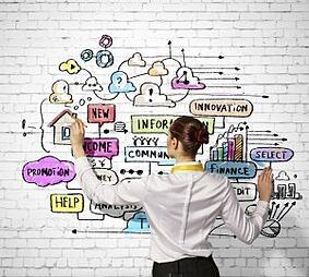 Women Drawing Buzzwords on White Brick Wall